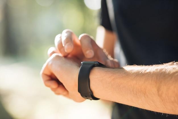 Inteligentny zegarek na męskiej dłoni na świeżym powietrzu