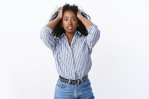 Intensywna afroamerykanka z kręconymi włosami panika trzymająca włosy rozszerzające się oczy dysząca zszokowany popełniła ogromny błąd stojąc otępiała przerażona oszołomiona straszna skomplikowana sytuacja, biała ściana