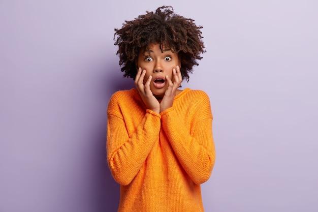 Intensywna nerwowa, przerażona ciemnoskóra kobieta sapie ze strachu, trzyma ręce na policzkach, jest w odrętwieniu