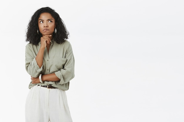 Intensywnie inteligentna i przemyślana, ładna kobieta w szarym t-shircie i spodniach, marszcząca brwi, wpatrująca się w prawy górny róg i myśląca