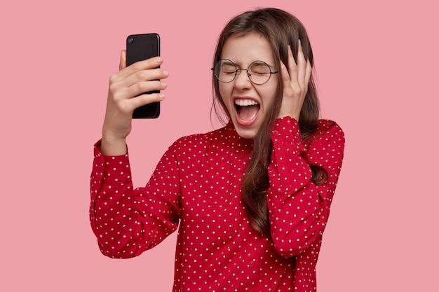 Intensywnie niezadowolona kobieta krzyczy ze złości, prowadzi z mężem rozmowę wideo przez smartfon, głośno krzyczy, trzyma rękę na głowie