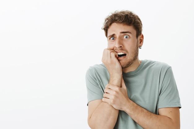 Intensywnie przestraszony przystojny mężczyzna czuje się przestraszony i zszokowany, gryzie paznokieć i wpatruje się w wytrzeszczone oczy