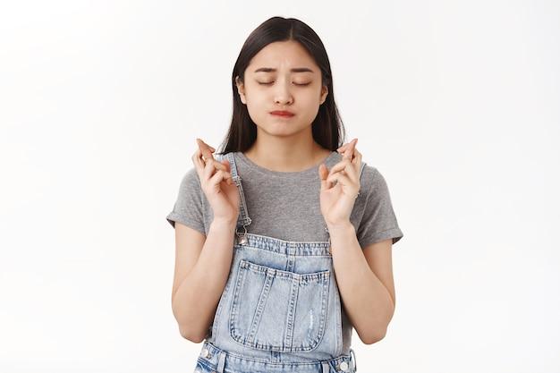 Intensywnie zmartwiona młoda azjatycka studentka modląca się do egzaminów dobrze spięte zamknij oczy ssać usta poważna z nadzieją modląca się skrzyżowanymi palcami powodzenia w oczekiwaniu spełnienia życzenia cud się wydarzył
