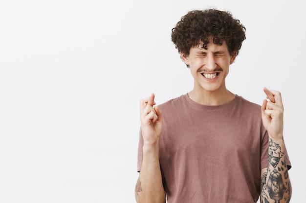 Intensywnie zmartwiony, pełen nadziei i wierny artystyczny stylowy facet z wąsami kręconymi włosami i tatuażami zaciskającymi zęby zamykającymi oczy i trzymającymi kciuki na szczęście podczas snucia życzeń nad szarą ścianą