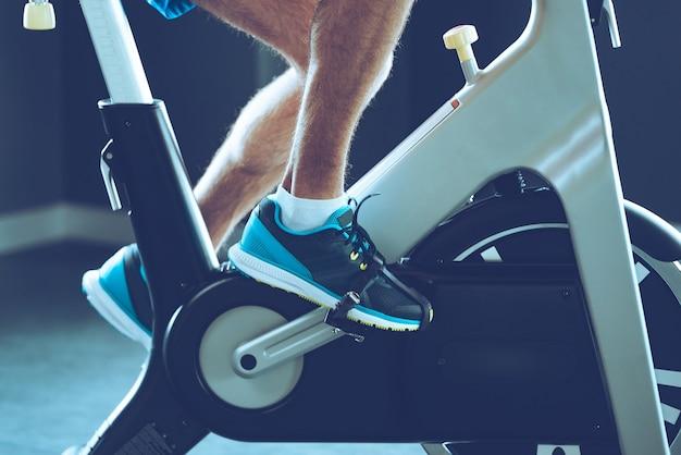 Intensywny trening cardio. widok z boku z bliska część młodego mężczyzny w butach sportowych na rowerze na siłowni