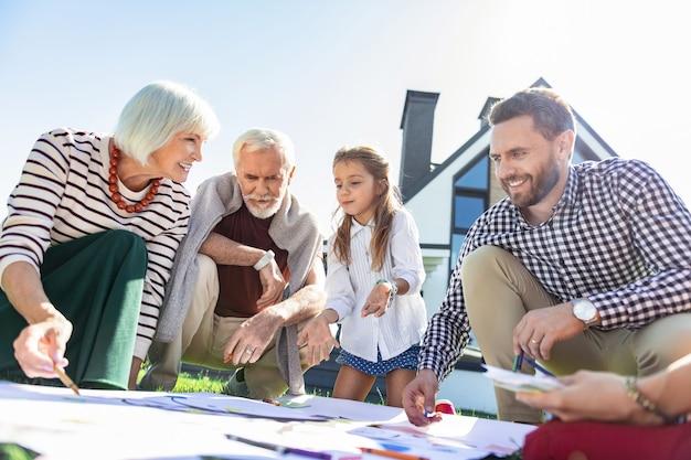 Interakcja rodzinna. szczęśliwy brodaty mężczyzna trzymając uśmiech na twarzy podczas włączania kreatywności