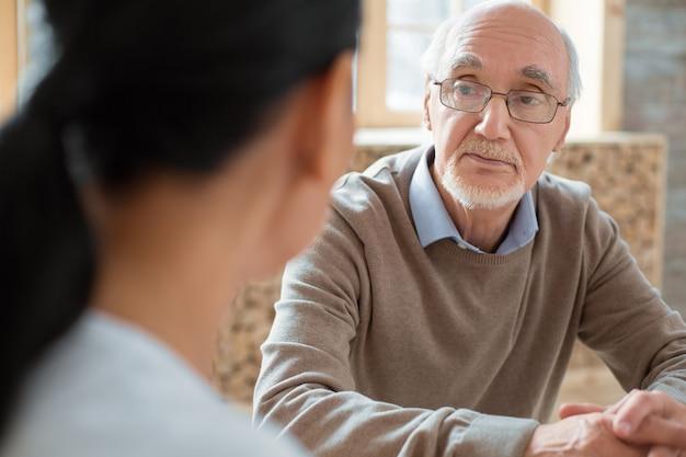 Interakcji społecznych. przystojny pozytywny starszy mężczyzna w okularach podczas słuchania wolontariusza i pozowanie na niewyraźne tło