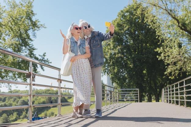 Interesujące miejsce. szczęśliwa miła para stojąca na moście podczas robienia zdjęć stamtąd