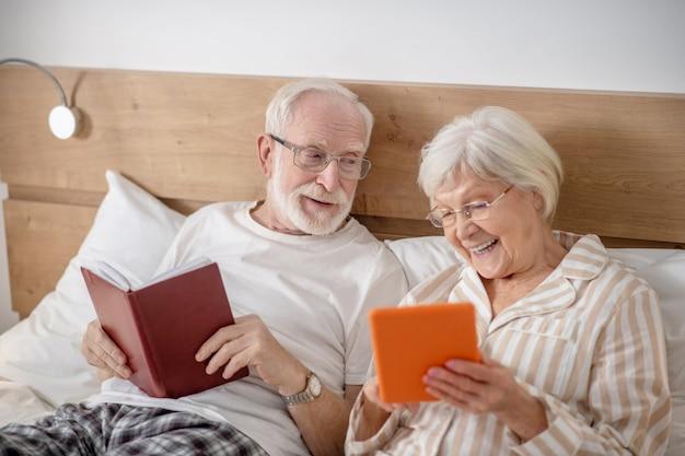 Interesujące rzeczy. starsze małżeństwo, leżąc w łóżku i miło spędzając czas podczas czytania