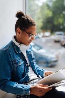 Interesujący artykuł. miły brunetka mężczyzna siedzący na parapecie i przygotowujący się do testu papierowego
