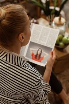 Interesujący Temat. Pilna, Spokojna Kobieta Zajęta Czytaniem Stron Magazynu O Urodzie Premium Zdjęcia