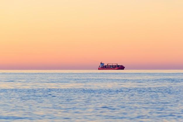 International container cargo statek na horyzoncie otwartego morza o zachodzie słońca. transport wodny międzynarodowy.