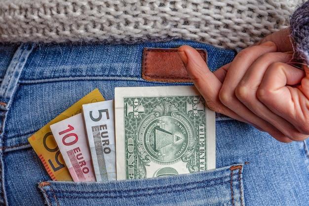 Internetowa koncepcja biznesu, zysków, podróży i finansów usd, aud i eur w tylnej kieszeni niebieskich dżinsów z żeńską ręką sięgającą po pieniądze