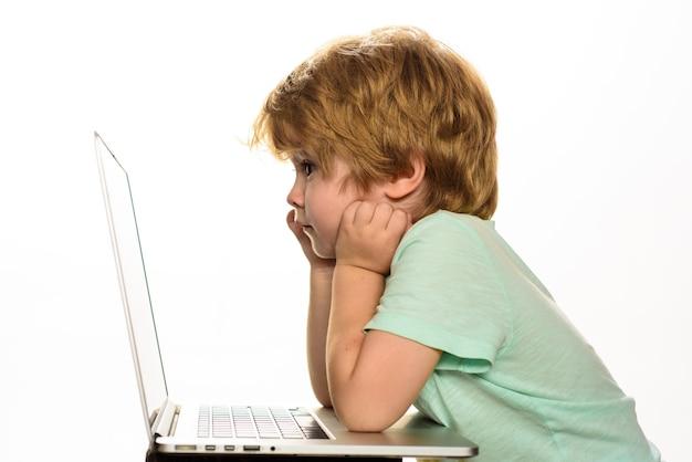 Internetowa praca domowa i chłopiec z mediów społecznościowych spędzający czas z notebookiem i nowoczesną technologią mały chłopiec