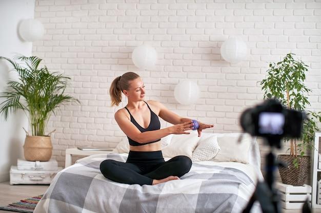Internetowy trener strumieniowy pokazuje technikę masażu piłki do ćwiczeń. rozluźnienie mięśni dłoni piłką do masażu. w nowoczesnym środowisku domowym.