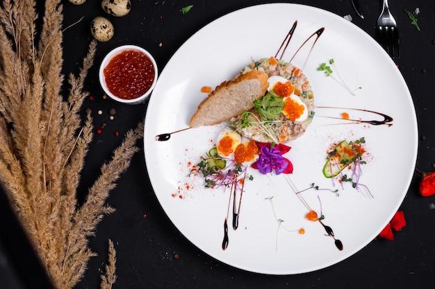 Interpretacja sałatki oliwkowej z grillowanym filetem z kurczaka, jajkiem przepiórczym i czerwonym kawiorem na ciemnej powierzchni. widok z góry