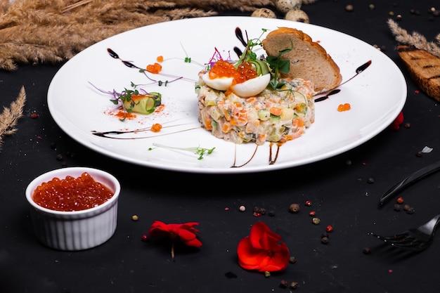 Interpretacja sałatki oliwkowej z grillowanym filetem z kurczaka, jajkiem przepiórczym i czerwonym kawiorem na ciemnej powierzchni.