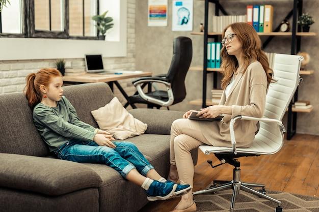 Introwertyczna dziewczyna. sprytny zawodowy psycholog rozmawia z pacjentem, próbując jej pomóc