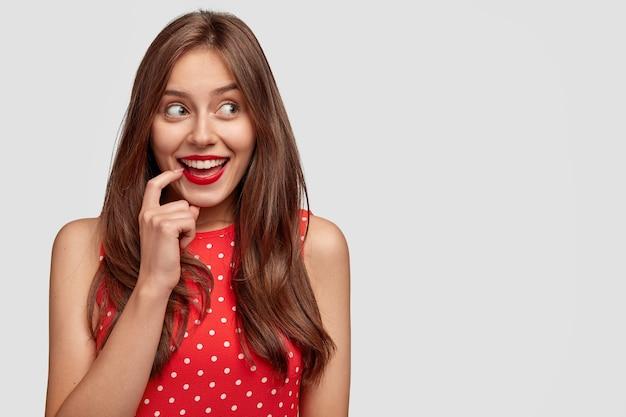 Intrygująca młoda kobieta rasy kaukaskiej z czerwonymi ustami, makijaż