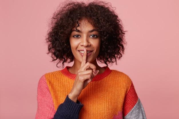 Intrygująca, tajemnicza dziewczyna z figlarnym, flirtującym uśmiechem, demonstruje gest ciszy, trzymając palec wskazujący przy ustach, wzywa do zachowania prywatności, sekretu, ciszy, spokoju.