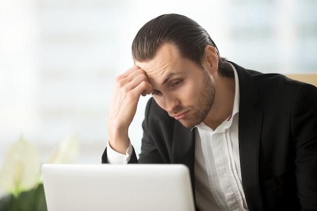 Intrygujący młody biznesmen patrzeje laptopu ekran