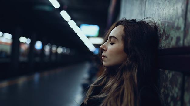 Intymny portret młodej kobiety relaksujący wewnątrz stacji metra. prawdziwy obraz stylu życia.