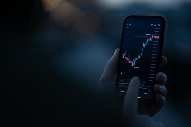 Inwestowanie online. męska ręka monitoruje dane giełdowe na smartfonie, używając aplikacji inwestycyjnej do analizy aktywności cenowej w czasie rzeczywistym. selektywna koncentracja na telefonie komórkowym z wykresem finansowym na ekranie