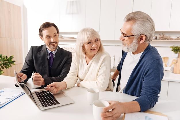 Inwestowanie w przyszłość. wesoły przemiły, biegły prawnik pracujący z kilkoma wiekowymi klientami, przedstawiając plan kontraktu i korzystając z nowoczesnego urządzenia
