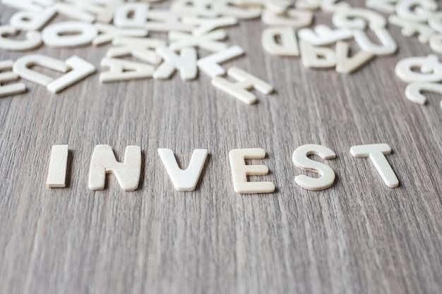 Inwestuj słowo drewniane litery alfabetu. koncepcja biznesowa i pomysł