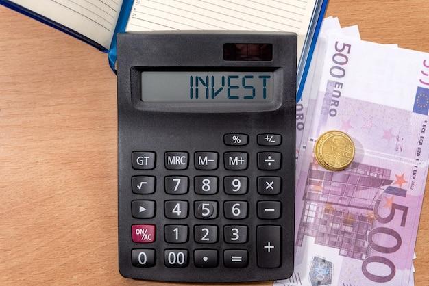 Inwestuj słowo na wyświetlaczu kalkulatora z bliska. koncepcja biznesowa i finansowa