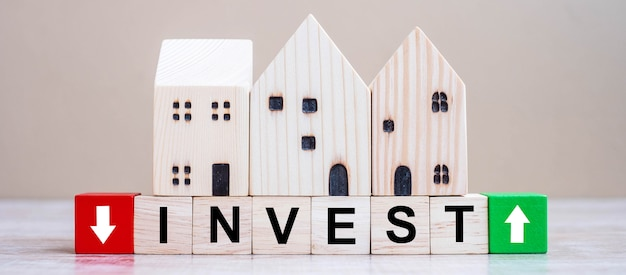 Inwestuj sześciany bloków z drewnianym domu modelu na tle tabeli.