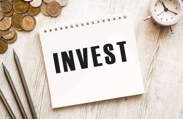 Inwestuj tekst na kartce notatnika. monety rozrzucone, ołówki na szarej drewnianej powierzchni
