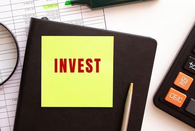 Inwestuj tekst na naklejce na pulpicie. pamiętnik, kalkulator i długopis. koncepcja finansowa.