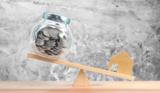 Inwestycja mieszkaniowa hipoteczna koncepcja finansowa domu, model domu i monety pieniężne bilansujące na huśtawce