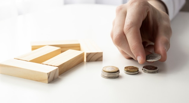 Inwestycja w nieruchomości i koncepcja finansowa hipoteki domu, ręczne umieszczenie stosu monet z drewnianym domu