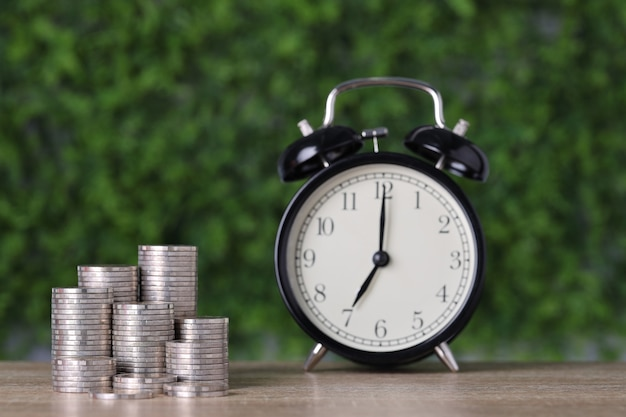 Inwestycje biznesowe i wzrost oszczędności dla koncepcji reklamy. układanie monet rosnących z zegarem na drewnianym stole i zielonym tle przyrody, co oznacza podatek lub zarabianie pieniędzy