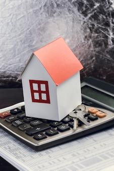 Inwestycje w nieruchomości. dom, klucz i kalkulator na stole
