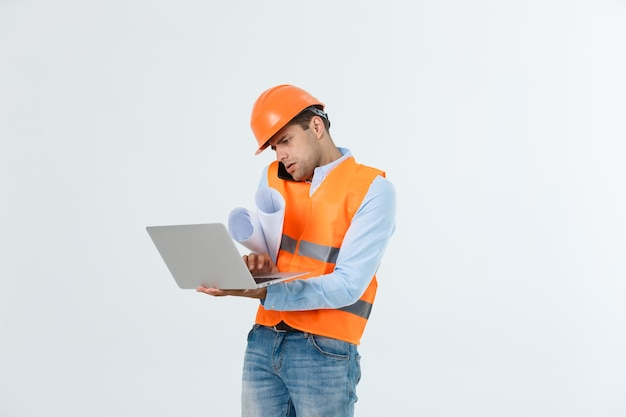 Inżynier, architekt, o zajętej twarzy, mówi na smartfonie, trzymając plany. mężczyzna, brygadzista w kasku mówiący na telefon, czerwone tło. architekt wzywa inżyniera do naprawy planu. koncepcja komunikacji.