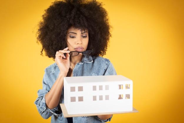Inżynier biznesu, architekt, twórca projektu, mieszana afroamerykańska kobieta, całkiem szczęśliwa, uśmiechnięta, w okularach, żółte tło