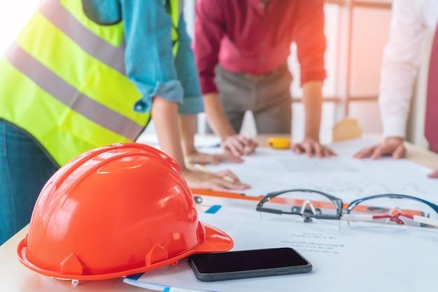 Inżynier budowlany kapelusz na stole konferencyjnym na spotkanie branżowe.
