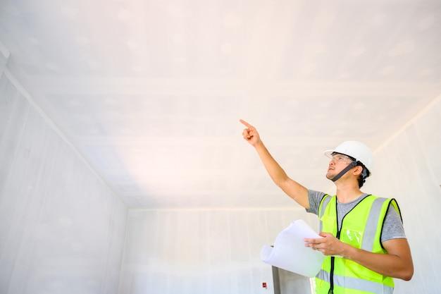Inżynier budowlany lub architekt posiadający dokumenty projektowe obejrzyj prace wewnętrzne i sprawdź ściany i sufity domu podczas projektowania na placu budowy.