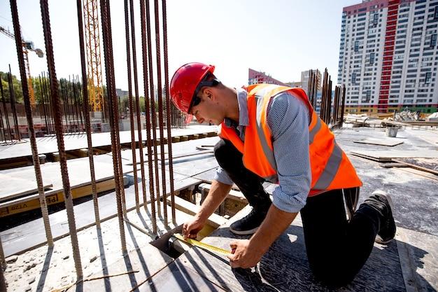 Inżynier budowlany ubrany w koszulę, pomarańczową kamizelkę roboczą i hełm mierzy otwór taśmą mierniczą na placu budowy.