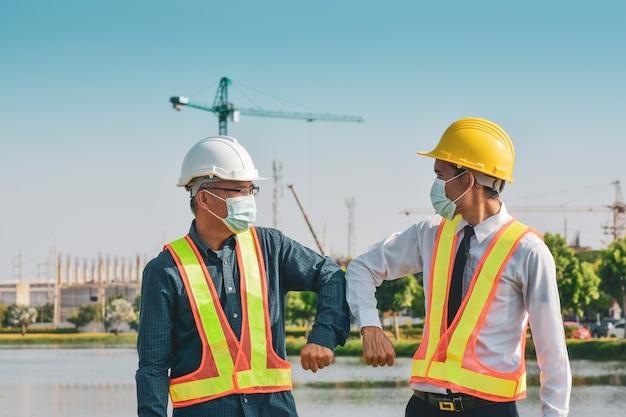Inżynier budowlany uścisnąć dłoń bez dotykania na placu budowy