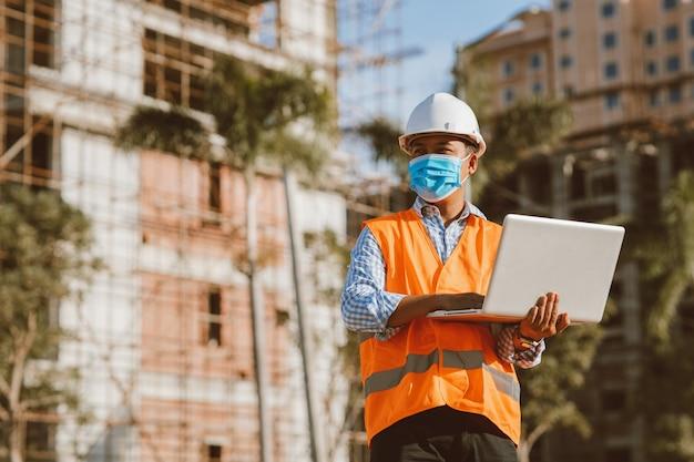 Inżynier budowlany w masce ochronnej przed rozprzestrzenianiem się chorób covid 19 podczas inspekcji na budowie z laptopem. koncepcja bezpieczeństwa