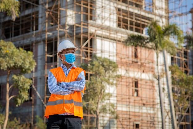Inżynier budowlany w masce ochronnej przed rozprzestrzenianiem się chorób covid 19 podczas inspekcji na placu budowy. koncepcja bezpieczeństwa