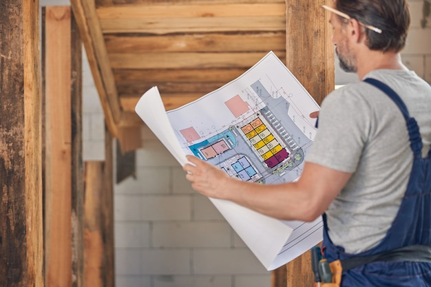 Inżynier budownictwa lądowego z ołówkiem za uchem, przeglądający rysunek