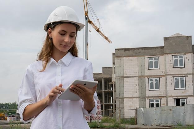 Inżynier budownictwa lądowego za pomocą tabletu w miejscu pracy na budowie