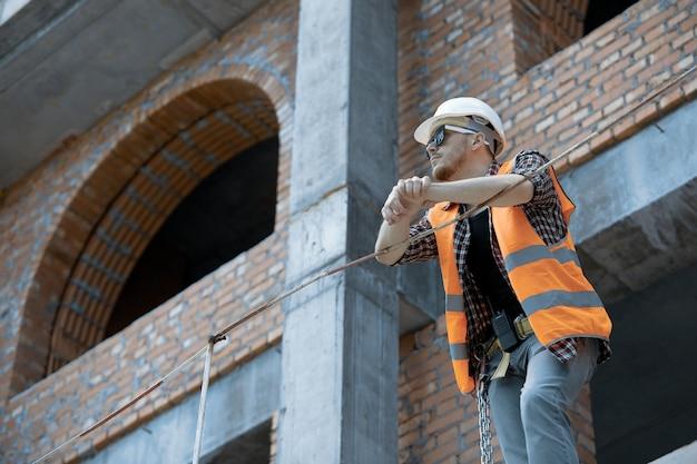 Inżynier budownictwa na wysokości w pomarańczowej kamizelce, białym kasku i okularach przeciwsłonecznych