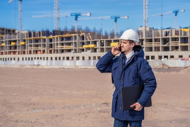Inżynier budownictwa w białym hełmie rozmawia przez telefon na budowie.