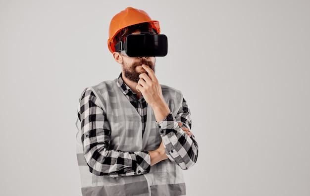 Inżynier budownictwa w okularach wirtualnej rzeczywistości 3d i pomarańczowym kasku na głowie. wysokiej jakości zdjęcie